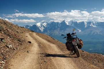 Motorcycle enduro traveler with suitcases standing alone on yellow stone extreme road path on the background of  high snow glacier ranges Altai mountains Siberia Russia Fototapete