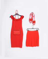 Fashion concept-red sundress in hanging and, skirt, shoes,bag on a white background