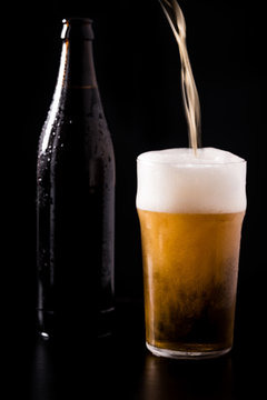 Pouring crafted unfiltered beer with foam in glass with bottle behind isolated on black dark background with soft reflections and beautiful shadows. Studio shot.