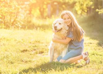 Teen girl hugging her golden retriever
