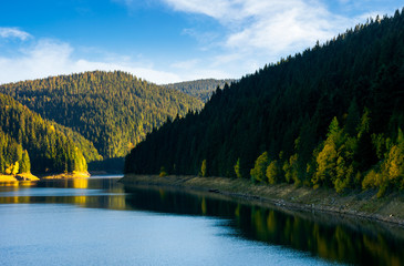 storage reservoir in mountain at sunrise. beautiful  landscape in early autumn