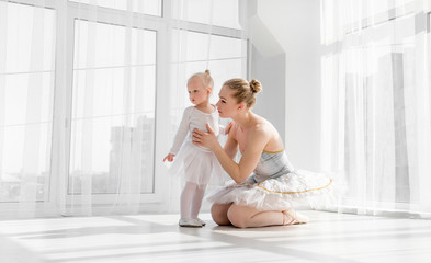 Young mother hugging little smiling daughter in ballet studio