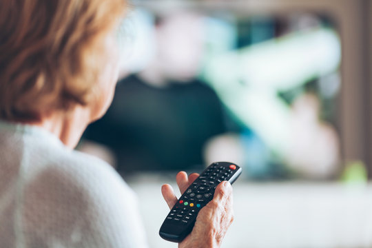 Senior woman with remote control watching tv