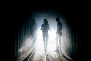 Light at the end of the tunnel. Silhouette of people in dark passage