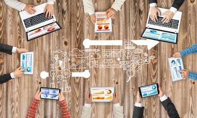 Top view of businesspeople sitting at table and using gadgets