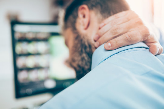 Office worker with neck pain from sitting at desk all day