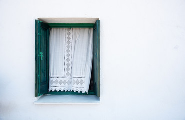 Wooden green window on a white wall