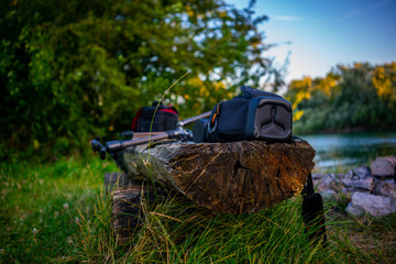 Photography gear on a wooden bench in front of a beatiful river