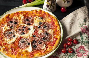 Delicious Italian pizza with spicy salami. Lunch is high in calories,