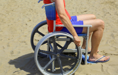 man with wheelchair on the beach in summer