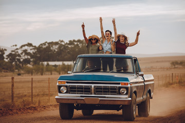 Excited friends traveling by a pickup truck