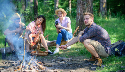 Company having hike picnic nature background. Hikers sharing impression of walk and eating. Summer hike. Picnic with friends in forest near bonfire. Tourists with camera relaxing checking photos