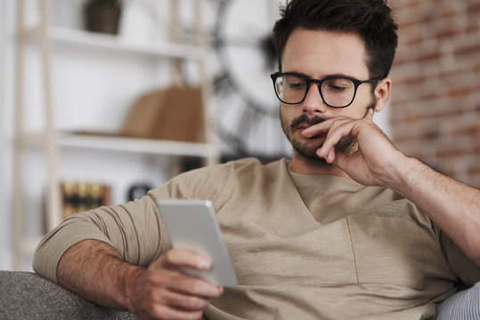 Man sitting on couch at home looking at smartphone