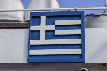 Greek flag carving from wooden piece hanged on boat