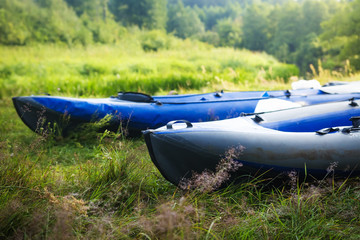 Kayaks on the grass on the river bank. Boats or canoes.