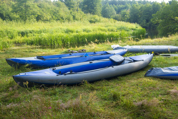 Kayaks for rafting along the river on the river bank. Boats or canoes on the river shore.