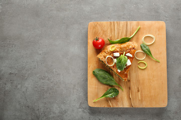 Piece of tasty pie with spinach on wooden board