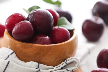 Bowl with ripe juicy plums on table