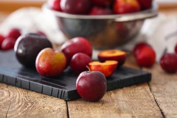 Ripe juicy plums on wooden board
