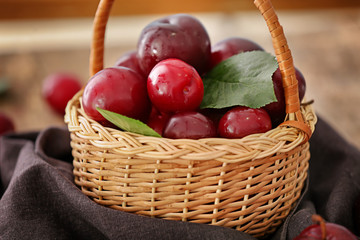Wicker basket with ripe juicy plums on table