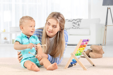 Baby and mother playing with toy abacus at home