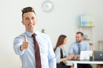 Young businessman showing thumb-up in conference room