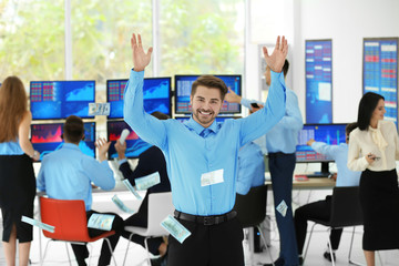 Happy male stock trader throwing dollar bills in office