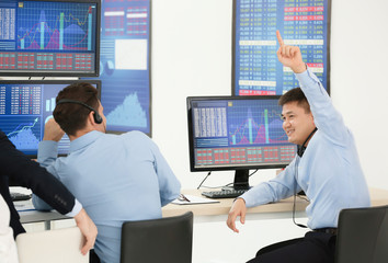 Male stock traders working in office