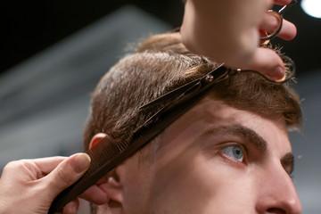Female hairdresser cutting client's hair, closeup