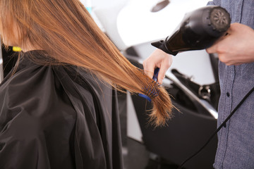 Professional stylist blow drying woman's hair in salon, closeup