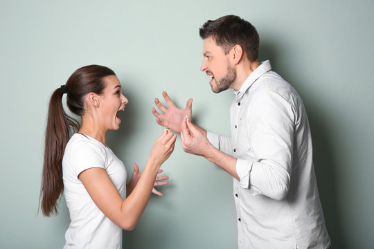 Young couple arguing on color background