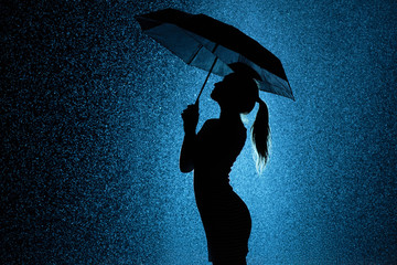 silhouette of the figure of a young girl with an umbrella in the rain