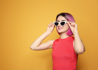Young woman with trendy hairstyle wearing sunglasses against color background