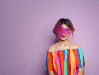 Young woman with trendy hairstyle against color background