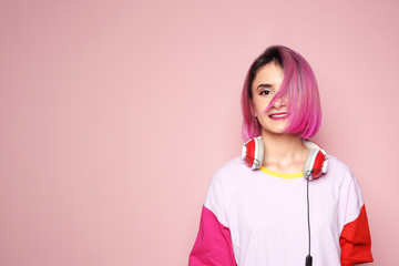 Young woman with trendy hairstyle and headphones against color background