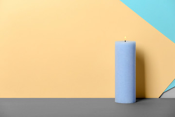 Decorative wax candle on table against color background
