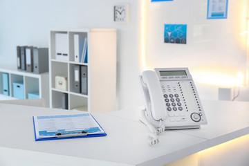 Telephone on reception desk in modern hospital