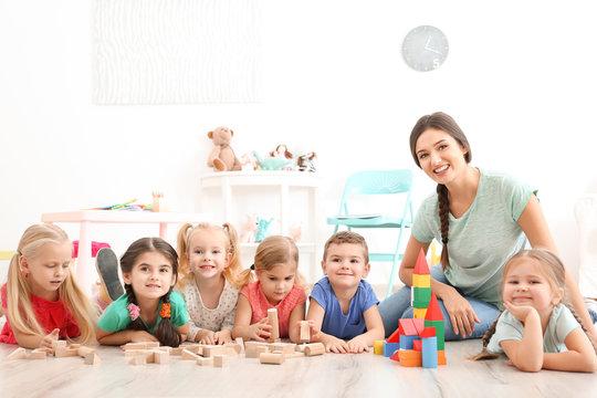 Cute little children playing with blocks in kindergarten