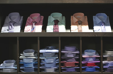 Classic men's shirts with neckties on shelves in boutique