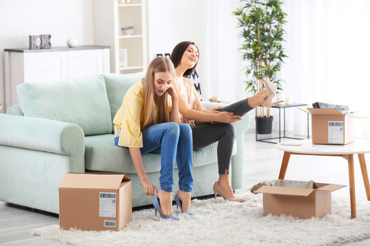 Young women trying on new shoes at home. Parcel delivery