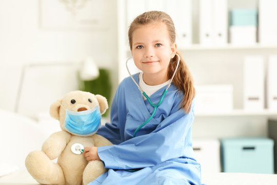 Cute little girl in doctor uniform playing with toy bear in hospital