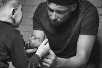 Little child giving piece of bread to homeless poor man