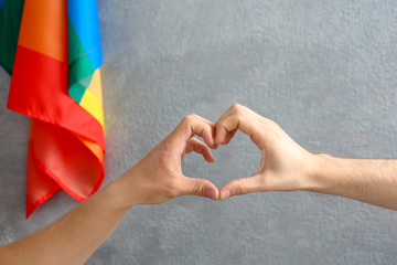 Gay couple making heart symbol with hands near rainbow flag