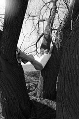 Black and white photo. A young man in jeans and a T-shirt is sitting or hanging between two trees. Looks at the camera. Hand curled behind his head.