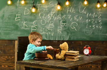 Lunch time. Little child feed teddy bear during lunch time. Boy enjoy lunch time with toy friend in school. Lunch time in elementary school. Eat for life