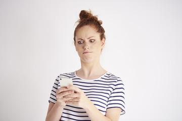 Furious woman using mobile phone at studio shot