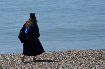 A woman wearing a 'mortar board' hat walks on the beach, following a graduation ceremony for students at University of Brighton, in Brighton
