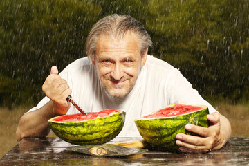 Man eating watermelon on table in summer rainy day park