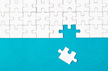 White puzzle pieces and place on blue background.