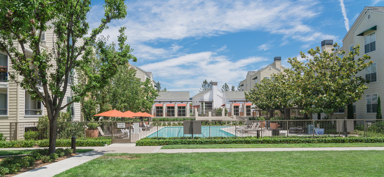 Common apartment building complex in Palo Alto, California, USA with fenced guard swimming pool. Summer cloud blue sky